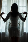 Женщина стоя близко окно Стоковая Фотография RF