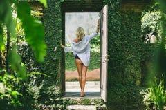 Женщина стоя в космосе двери сада стоковое изображение rf