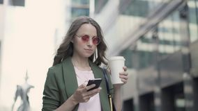 Женщина стоя в кофе сети улицы города занимаясь серфингом и выпивая акции видеоматериалы