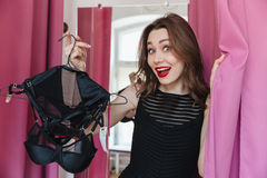 Женщина стоя в магазине одежды внутри помещения держа женское бельё Стоковая Фотография