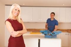 Женщина стоя в новой кухне приспособленной роскошью Стоковые Изображения