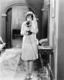 Женщина стоя в прихожей говоря на телефоне подсвечника (все показанные люди более длинные живущие и никакое имущество не существу Стоковые Изображения