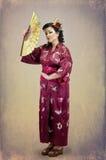 Женщина стоя в традиционных национальных дальневосточных одеждах с Стоковые Фото