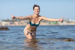 Женщина стоя колен-глубокий в море и больших пальцах руки выставок вверх Стоковые Изображения