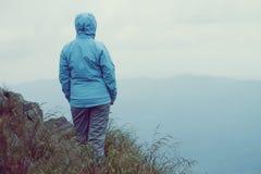 Женщина стоя над скалой Стоковая Фотография