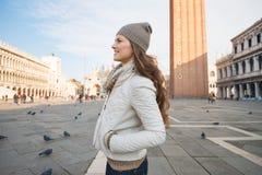 Женщина стоя на аркаде Сан Marco и смотря в сторону Стоковое Фото