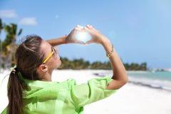 Женщина стоя на белом песке делая форму Харта с пальцами Стоковое фото RF