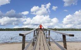 Женщина стоя на детях деревянной пристани наблюдая плавая Стоковое Изображение RF