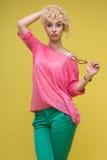 Женщина стоя на желтой предпосылке Стоковые Фото