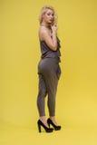 Женщина стоя на желтой предпосылке Стоковые Фотографии RF
