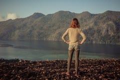 Женщина стоя на заливе горы обозревая Стоковая Фотография