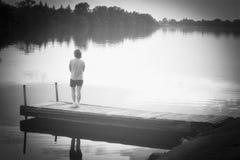 Женщина стоя на крае пристани наблюдая подачу озера Стоковые Изображения RF