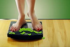 Женщина стоя на масштабах, вес теряет Стоковые Фото