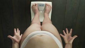 Женщина стоя на масштабах с словом брюзгливым на экране, неудачный надоеданный dieting, видеоматериал