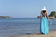 Женщина стоя на пляже и держа пары тапочек Стоковая Фотография RF