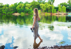 Женщина стоя на речном береге Стоковые Изображения