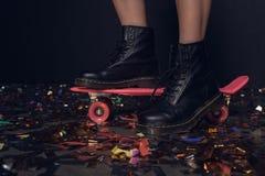 Женщина стоя на скейтборде во время партии Стоковая Фотография