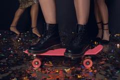Женщина стоя на скейтборде с друзьями позади во время партии Стоковая Фотография RF