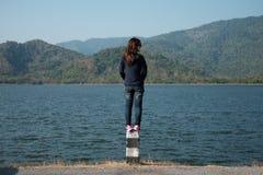 Женщина стоя на фронте обочины штендера ее имеет большое озеро и Стоковые Фото
