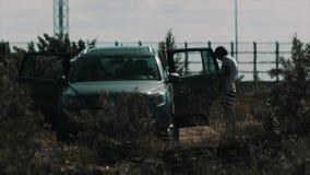 Женщина стоя около открытой автомобильной двери на природе около hightway акции видеоматериалы