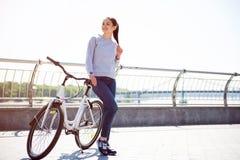 Женщина стоя около велосипеда Стоковое фото RF