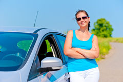 Женщина стоя около его автомобиля на проселочной дороге Стоковое Фото