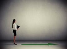 Женщина стоя около зеленой стрелки Стоковые Фото
