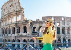 Женщина стоя около Colosseum в Риме слушая к музыке Стоковые Фотографии RF
