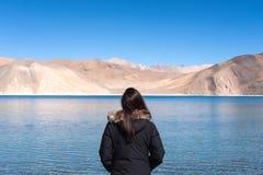 Женщина стоя перед озером Pangong с Mountain View и голубым небом Стоковая Фотография RF