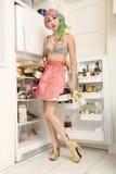 Женщина стоя перед холодильником с бутылкой вина Стоковые Фото