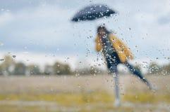 Женщина стоя под зонтиком с дождевыми каплями дальше Стоковые Изображения