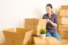 Женщина стоя среди картонных коробок Стоковые Изображения