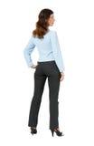 Женщина стоя с его задней частью на белой предпосылке стоковое изображение