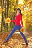 Женщина стоя с листьями в парке осени Стоковые Фотографии RF