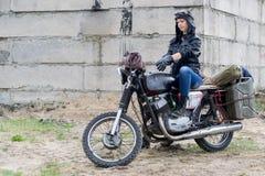 Женщина столба апоралипсическая на мотоцикле около разрушенного здания Стоковое фото RF