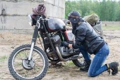 Женщина столба апоралипсическая около мотоцикла около разрушенного здания Стоковая Фотография RF