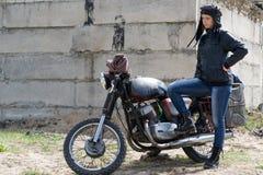 Женщина столба апоралипсическая около мотоцикла около разрушенного здания Стоковое Изображение