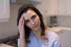 Женщина страдая от головной боли в кухне Стоковые Фотографии RF
