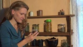 Женщина страны льет специи гвоздичного дерева в малый стеклянный опарник 4K акции видеоматериалы