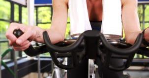 Женщина сфокусированная пригонкой задействуя на велотренажере сток-видео