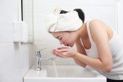 Женщина счастливая очищает кожу с пеной на раковине стоковое изображение