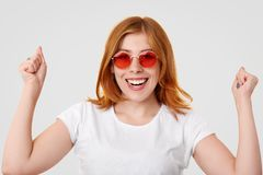 Женщина счастливого успешного имбиря молодая держит сжатые кулаки поднятый, имеет зубастую улыбку, празднует успешный день, одеты стоковое изображение