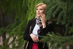 Женщина счастливой молодой моды белокурая идя в парк города стоковое изображение