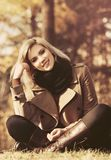 Женщина счастливой молодой моды белокурая сидя на траве в лесе осени Стоковые Фотографии RF