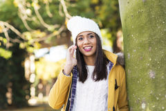 Женщина счастья красивая латинская с шляпой говоря телефоном стоковая фотография