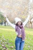 Женщина счастья положительная с руками шляпы и шарфа распространяя, вне стоковые фотографии rf