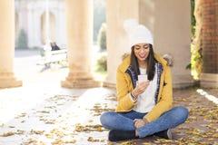 Женщина счастья при шляпа смотря messahe в телефоне, st осени стоковые изображения