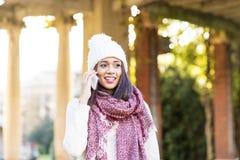 Женщина счастья с крышкой и шарфом говоря телефоном, внешним стоковое изображение