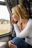 Женщина ся и смотря вне окно поезда Стоковые Изображения RF