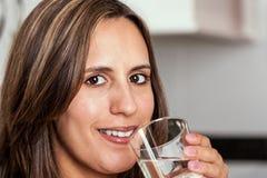 Женщина ся с стеклом воды Стоковая Фотография